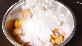 A farinha cai em uma placa dos abricós com açúcar filme