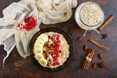 Farinha de aveia deliciosa e saudável com banana, sementes da romã, amêndoa e canela fotografia de stock