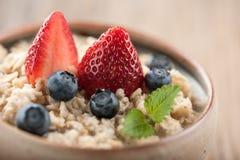Farinha de aveia do café da manhã com leite e bagas Foto de Stock