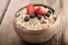 Farinha de aveia do café da manhã com leite e bagas Fotografia de Stock