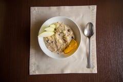 Farinha de aveia do café da manhã com maçã, passas na tabela Imagem de Stock Royalty Free