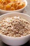 Farinha de aveia e flocos de milho na bacia cerâmica branca Foto de Stock