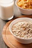 Farinha de aveia e flocos de milho nas bacias brancas na placa de madeira Imagem de Stock