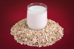 Farinha de aveia em torno de um vidro do leite em um fundo vermelho Foto de Stock