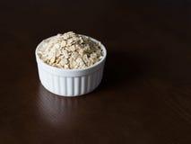 Farinha de aveia em um piala branco em uma tabela de madeira escura Fotos de Stock Royalty Free