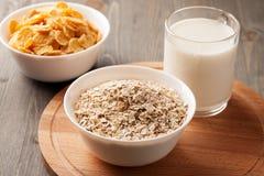 Farinha de aveia, flocos de milho e vidro do leite na placa de madeira Fotos de Stock Royalty Free