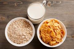 Farinha de aveia, flocos de milho e vidro do leite na tabela de madeira Fotos de Stock