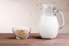 A farinha de aveia lasca-se em uma bacia ao lado da garrafa do leite Fotos de Stock