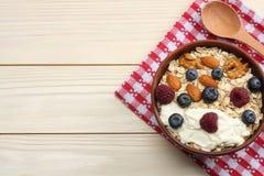 farinha de aveia, mirtilos, framboesas e porcas saudáveis do café da manhã na tabela de madeira branca Vista superior com espaço  Foto de Stock