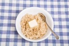 Farinha de aveia quente com manteiga e colher Foto de Stock Royalty Free