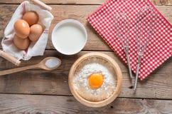 A farinha em uma bacia, em um ovo, em um leite e em um chicote de madeira para bater Fotos de Stock Royalty Free