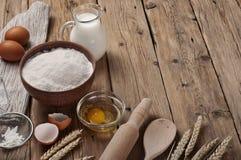 Farinha, ovo, leite na cozinha rústica da tabela de madeira Foto de Stock