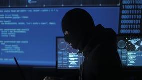 Farlig en hacker i maskeringsförsöken att skriva in systemet genom att använda koder och nummer för att finna ut säkerhetslösenor stock video