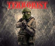 Farlig maskerad och beväpnad man med terroristtecknet på grungy bac royaltyfri foto
