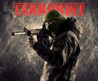 Farlig maskerad och beväpnad man med terroristtecknet på grungy bac fotografering för bildbyråer
