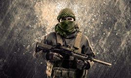 Farlig maskerad och beväpnad man med terroristtecknet på grungy bac royaltyfri fotografi