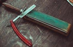 Farlig rakkniv för tappning med lädervässaren Royaltyfri Fotografi