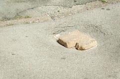 Farlig skada på asfaltvägen med tegelstenar i den öppna hålfaran för medelkörning arkivfoto