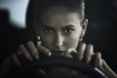 Farlig skönhetkvinna som kör en bil, slut upp ståenden Arkivbilder