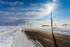 Farlig snöa tom väg med övergångsställe, hållplatsen och vägmärken för körning av bilar och av kollektivtrafik under häftig snöst Arkivbild