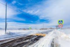 Farlig snöa väg med övergångsställe, hållplatsen och vägmärken för körning av bilar och av kollektivtrafik under häftig snöstorm Fotografering för Bildbyråer