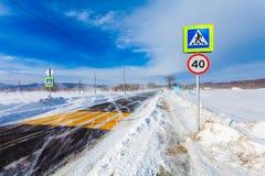 Farlig snöa väg med övergångsställe, hållplatsen och vägmärken för körning av bilar och av kollektivtrafik under häftig snöstorm Arkivbild
