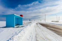 Farlig snöa väg med den tomma hållplatsen och vägmärken i lantligt för körning av bilar och av kollektivtrafik under häftig snöst Arkivbild
