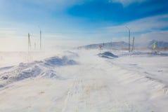 Farlig snöa väg med vägmärken för körning av bilar och av kollektivtrafik under häftig snöstorm Arkivfoton