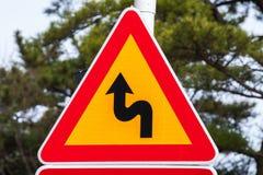 Farliga vänd, varningstrafiktecken Royaltyfri Bild