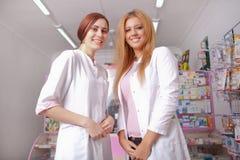 Farmácia interna de duas enfermeiras felizes dos jovens foto de stock