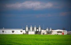 Farm. Dairy farm barns, farmstead and several grain silos in an open field Stock Image