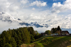Farm in the Alps. Small farm in the Alps with snowcapped mountains in the background Stock Image