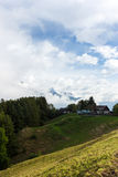 Farm in the Alps. Small farm in the Alps with snowcapped mountains in the background Royalty Free Stock Images