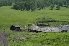 Farm, animal pen. Village among green hills, wooden old houses, summer, beautiful landscape Royalty Free Stock Photo