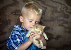 Farm boy holding a kitten and savoring the love Royalty Free Stock Photography