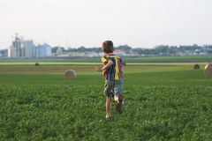 Farm boy running through field Stock Images