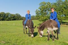 Farm Boys with their donkeys. Farm boys riding on their donkeys royalty free stock image