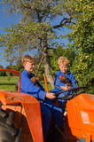 Farm Boys on tractor. Farm boys with chickens riding on orange tractor royalty free stock images