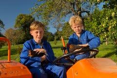 Farm Boys on tractor. Farm boys with chickens riding on orange tractor stock photos