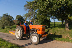 Farm Boys on tractor. Farm boys with chickens riding on orange tractor royalty free stock photo