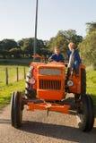 Farm Boys with tractor. Farm boys riding on orange tractor stock photo