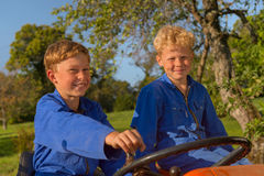 Farm Boys with tractor. Farm boys riding on orange tractor royalty free stock images