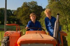 Farm Boys with tractor. Farm boys riding on orange tractor royalty free stock photos