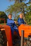 Farm Boys with tractor. Farm boys riding on orange tractor stock photography