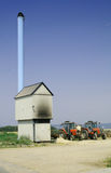 Farm building incinerator. Red tractors by incinerator providing energy or heating or power to farm. Blue chimney against blue sky stock image