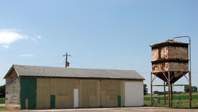 Farm Buildings. A view of a large utility or storage barn and a elevated grain tank, typical buildings on an agricultural farm Stock Photos