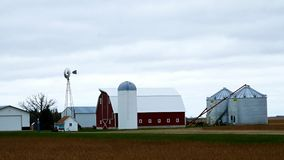Farm buildings with active windmill on a cloudy day in Minnesota