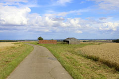 Farm buildings and footpath. Old farm buildings and barn overlooking the vale of york under a summer blue cloudy sky in the yorkshire wolds Royalty Free Stock Image