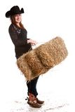 Farm Chores. Attractive young woman wearing a cowboy hat and bluejeans and carrying a bale of hay stock image