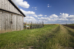 Farm in countryside. Exterior of wooden farm building in countryside under cloudscape Stock Images